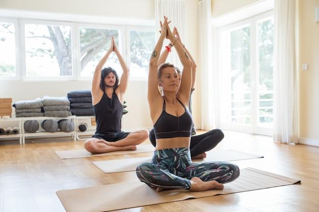 Fokussierte positive yogis, die in der turnhalle üben