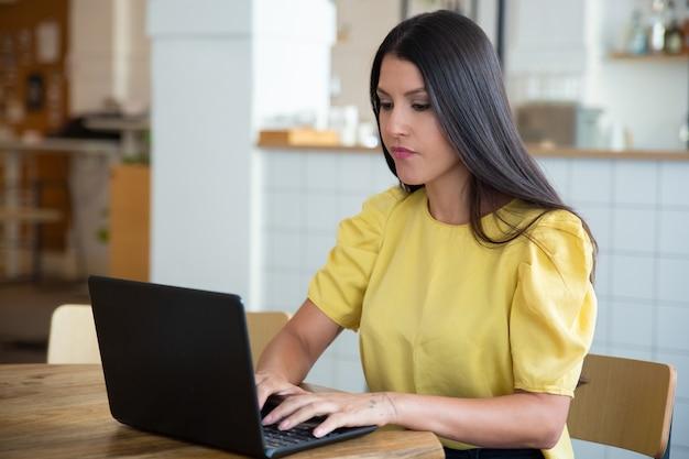 Fokussierte schöne schwarzhaarige frau, die am tisch im gemeinsamen arbeitsraum sitzt, laptop benutzt, anzeige betrachtet und tippt