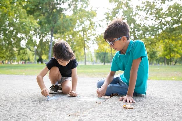 Fokussierte schwarzhaarige jungen, die mit bunten kreiden sitzen und zeichnen. konzept für kindheit und kreativität