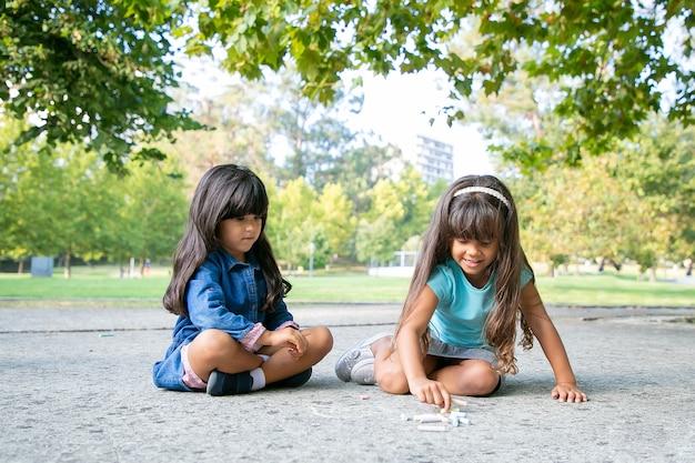 Fokussierte schwarzhaarige mädchen, die mit bunten kreidestücken auf asphalt sitzen und zeichnen. vorderansicht. konzept für kindheit und kreativität