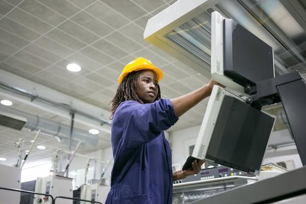Fokussierte selbstbewusste fabrikarbeiterin, die eine industriemaschine bedient, die steuerplatine berührt und ein tablet verwendet