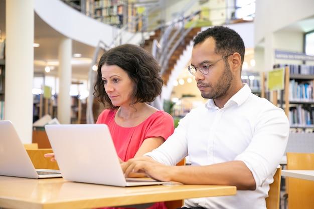 Fokussierte studenten, die in der bibliothek arbeiten
