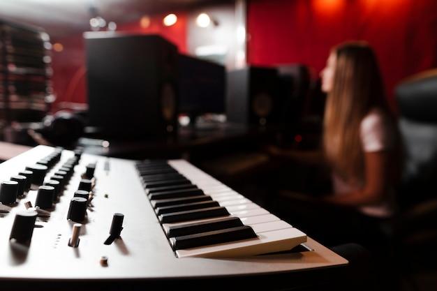 Fokussierte tastatur und unscharfe frau im studio
