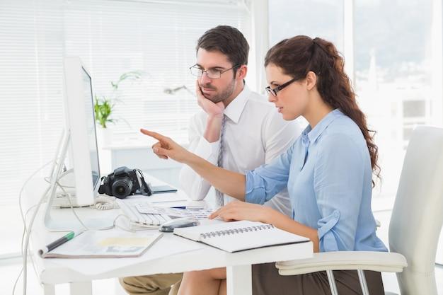 Fokussierte teamwork, die computer interagiert und zeigt