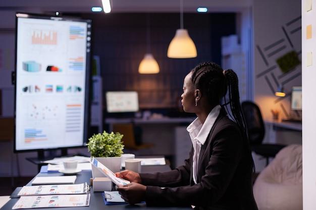 Fokussierte workaholic afroamerikanische geschäftsfrau, die bei der präsentation von finanzdiagrammen des unternehmens arbeitet