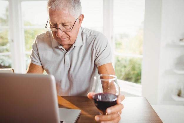 Fokussierter älterer mann, der zu hause laptop verwendet und wein trinkt