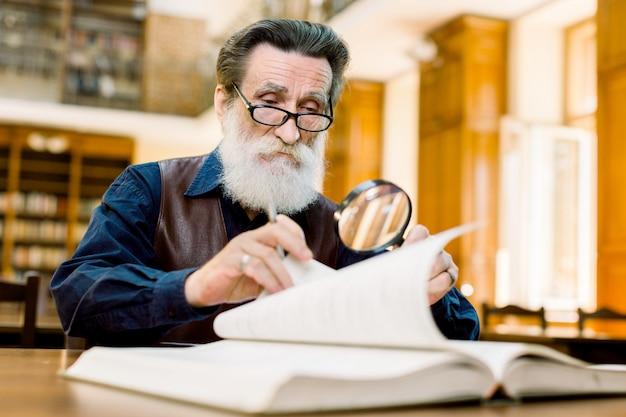 Fokussierter älterer stilvoller mannlehrer, universitätsprofessor, in brillen, die in der alten bibliothek sitzen