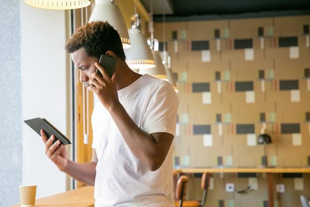 Fokussierter afroamerikaner, der auf zelle spricht und tablettbildschirm betrachtet