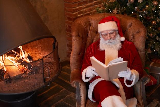 Fokussierter alter weihnachtsmann in brillen, der in einem bequemen sessel in der nähe des kamins sitzt und ein buch liest