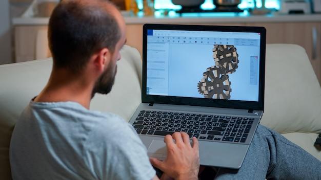 Fokussierter architekt, der einen laptop für die neuentwicklung eines technischen konstruktionsprototyps betrachtet