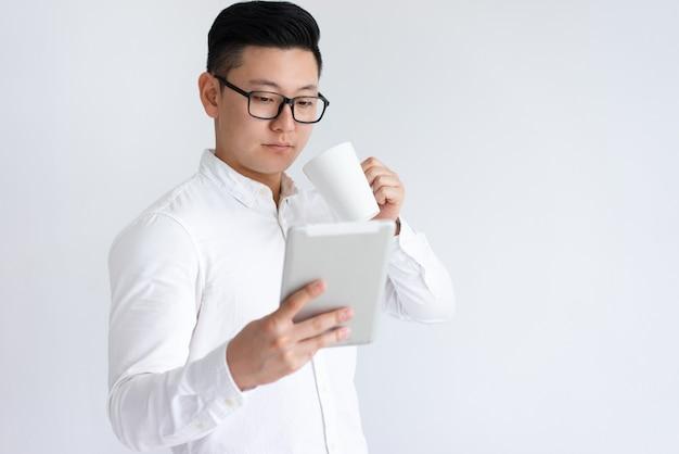 Fokussierter asiatischer mann, der tablette verwendet und kaffee trinkt