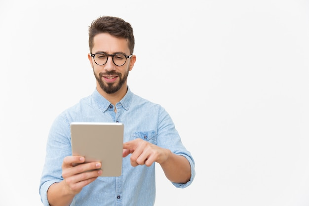 Fokussierter aufpassender inhalt des positiven kerls auf tablette