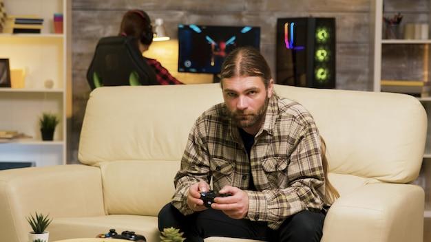 Fokussierter bärtiger mann, der auf der couch sitzt und videospiele mit drahtlosem controller spielt. freundin, die im hintergrund am computer spielt.