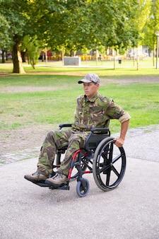 Fokussierter behinderter militärmann im rollstuhl, der tarnuniform trägt und fußweg im stadtpark hinunter bewegt. kriegsveteran oder behindertenkonzept