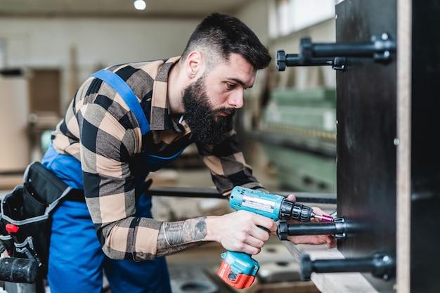 Fokussierter berufsschreiner, der in seiner werkstatt arbeitet, holzbearbeitungs- und handwerkskonzept.