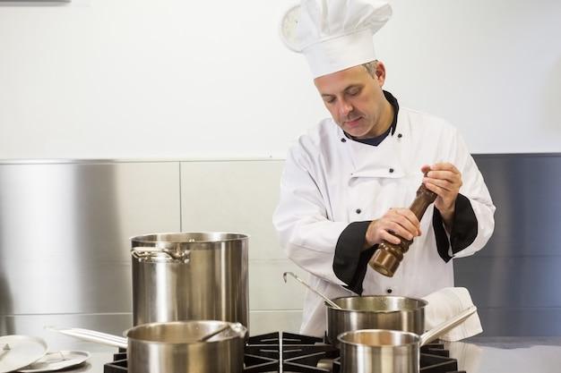 Fokussierter chefkoch, der pfeffermühle verwendet