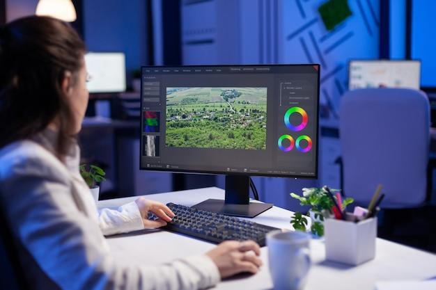 Fokussierter editor, retuschierbearbeiter, der den farbgrad auf einem professionellen computer bearbeitet Premium Fotos