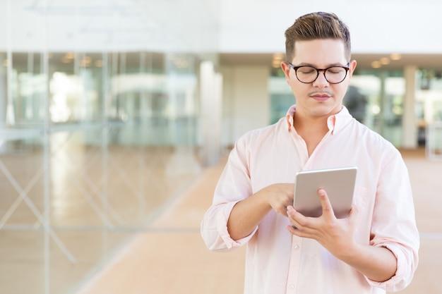 Fokussierter entwickler, der im flur steht und an tablette arbeitet