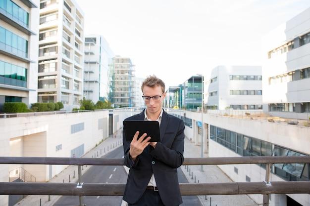 Fokussierter ernster fachmann, der an tablette arbeitet