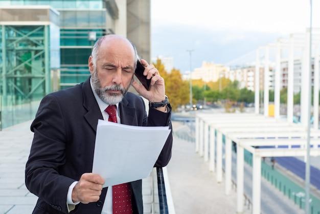 Fokussierter ernster reifer unternehmensleiter, der vertrag bespricht