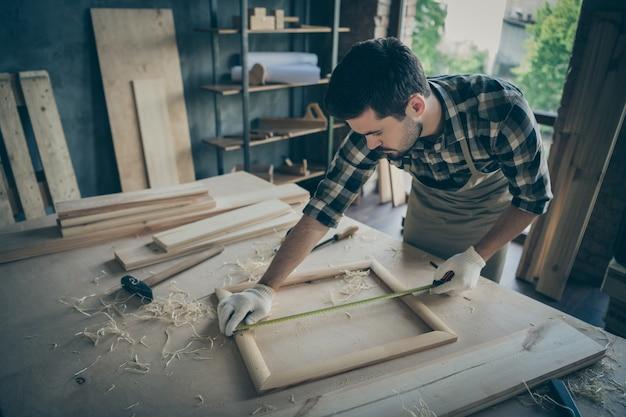 Fokussierter ernsthafter mann konzentrierte sich darauf, die länge des holzrahmens mit hilfe einer klebebandlinie richtig zu messen