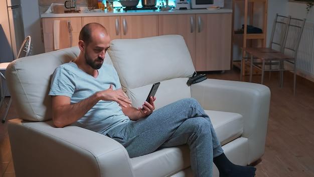 Fokussierter erwachsener, der mit freunden über social-media-verbindungen mit modernem smartphone spricht