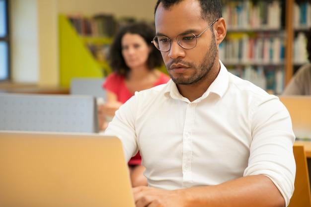 Fokussierter erwachsener männlicher student, der öffentlich bibliothek erforscht