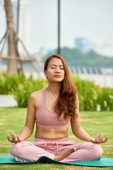 Fokussierter ethnischer mann, der draußen meditiert