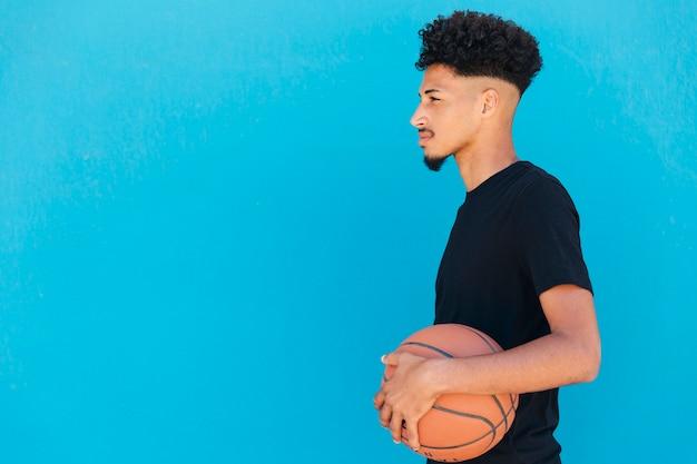 Fokussierter ethnischer spieler mit basketball