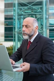 Fokussierter fälliger geschäftsmann mit laptop email überprüfend