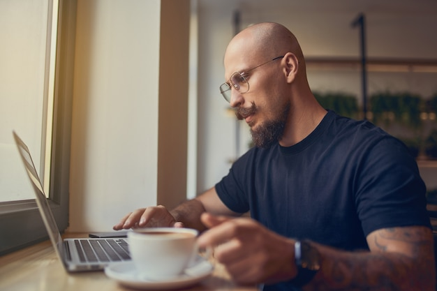 Fokussierter geschäftsmann arbeitet am pc, um die ergebnisse der verkaufsstatistik zu analysieren und grafiken zu lernen, während er im café sitzt