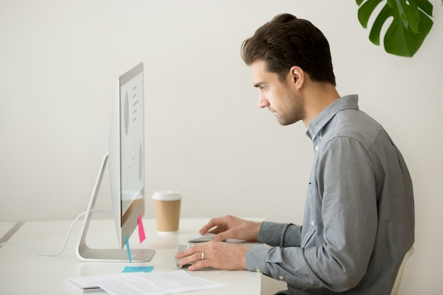 Fokussierter geschäftsmann, der an computer mit projektstatistik, seitenansicht arbeitet