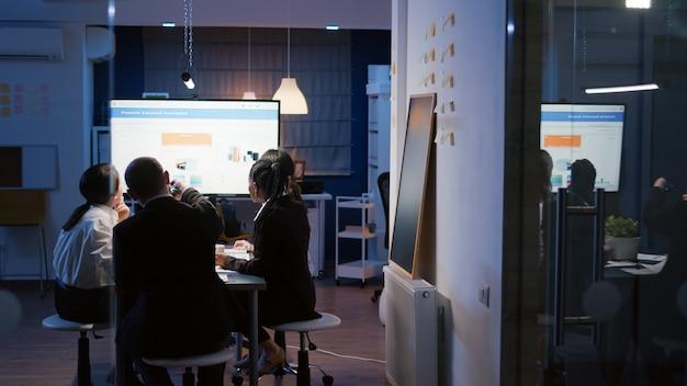 Fokussierter geschäftsmann, der die unternehmenslösung mit dem präsentationsmonitor präsentiert, der überstunden im besprechungsraum im büro macht