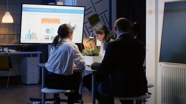 Fokussierter geschäftsmann, der die unternehmensstrategie mit dem präsentationsmonitor präsentiert