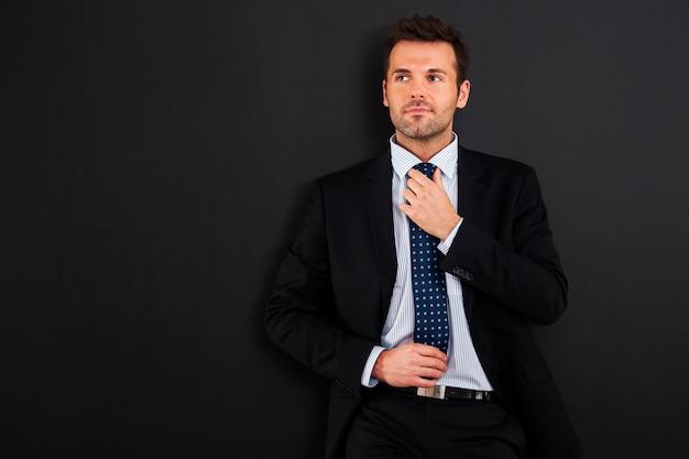 Fokussierter geschäftsmann, der krawatte gegen tafel trägt