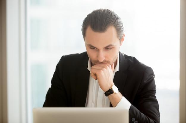 Fokussierter geschäftsmann, der lösung im internet sucht