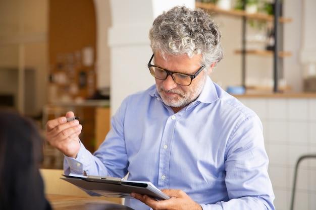 Fokussierter geschäftsmann, der vereinbarung beim treffen unterzeichnet