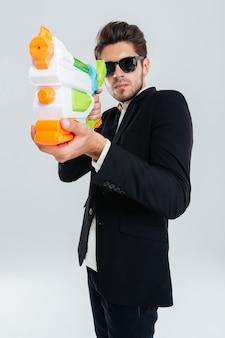 Fokussierter geschäftsmann in sonnenbrille und anzug, der mit wasserpistole über grauer wand schießt