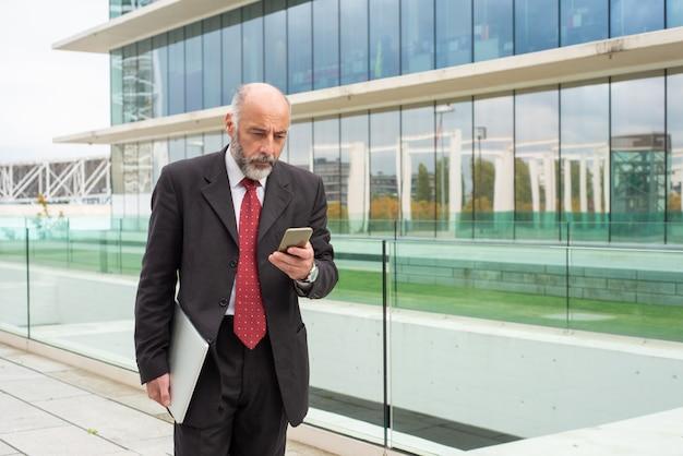 Fokussierter grauhaariger firmeninhaber, der smartphone verwendet