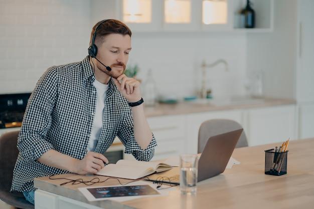 Fokussierter gutaussehender bärtiger mann, der am küchentisch sitzt und auf den laptop-bildschirm schaut, während er ein headset verwendet und einen stift hält, leute, die online studieren. fernarbeit zu hause und fernunterricht