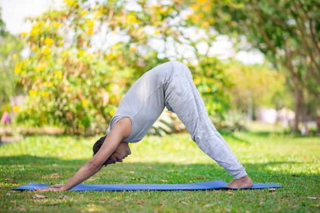 Fokussierter jogi, der auf parkgras trainiert. junger indischer mann, der abwärts gesicht des yoga hält