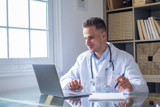 Fokussierter junger arzt mit brille, der im büro am laptop arbeitet, am schreibtisch sitzt, auf den bildschirm schaut, ernsthafter therapeut gp bericht oder e-mail schreibt, patienten online konsultiert, krankenkarte ausfüllt