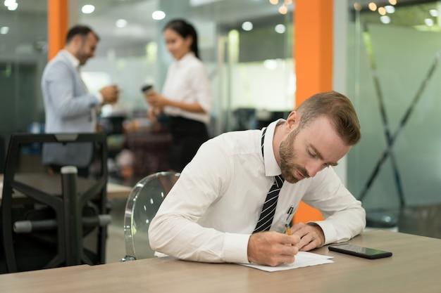 Fokussierter junger geschäftsmann, der anmerkungen macht und am schreibtisch arbeitet