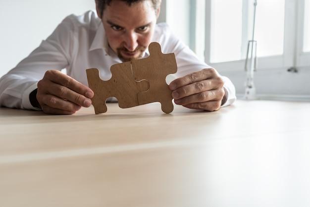 Fokussierter junger geschäftsmann, der zwei passende puzzleteile verbindet, während er an seinem schreibtisch sitzt. konzeptionelle der unternehmensfusion und -lösung.