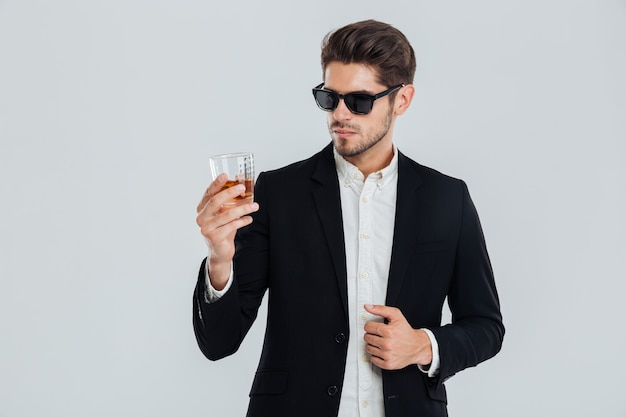 Fokussierter junger geschäftsmann in suite und sonnenbrille mit blick auf whisky im glas über grauer wand