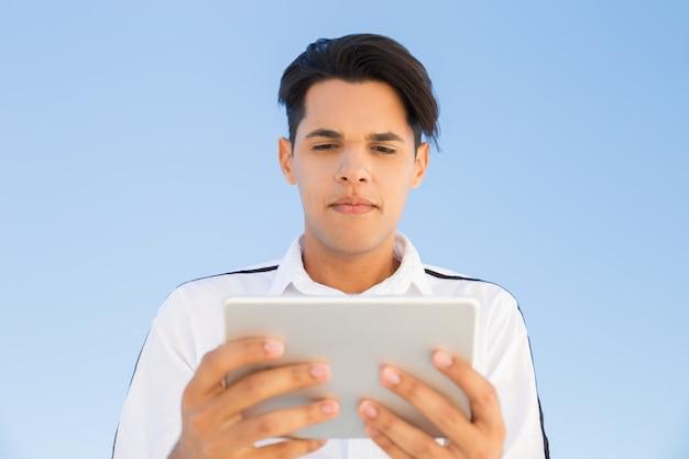 Fokussierter junger hispanischer mann, der draußen tablette verwendet