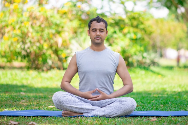 Fokussierter junger indischer mann, der in der lotoshaltung meditiert.