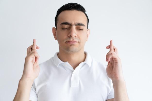 Fokussierter junger mann, der finger gekreuzt hält und augen schloss. wünschen sie konzept.