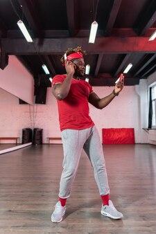 Fokussierter junger tänzer, der große kopfhörer trägt und auf dem smartphone schaut und musik auswählt