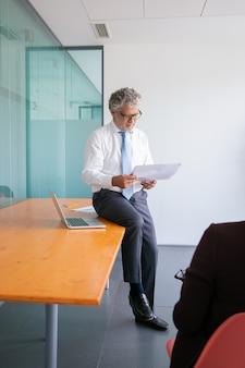 Fokussierter kaukasischer geschäftsmann, der auf tisch sitzt und dokument liest